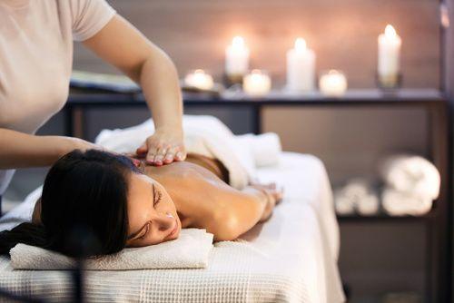 Körpermassage und Wellnessbehandlung im modernen Salon mit Kerzen