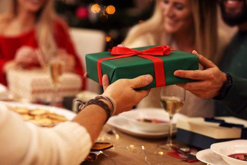 Gruppe Freunde, die zu Hause Weihnachtsgeschenke verteilen