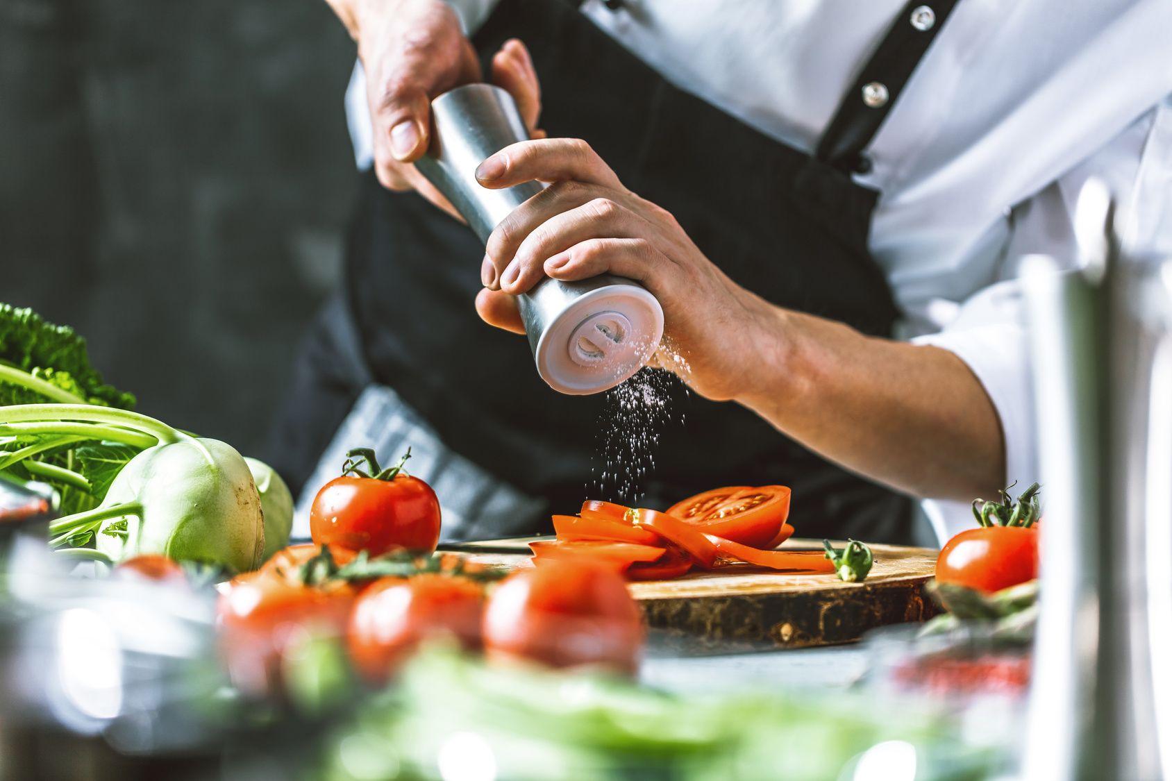 Chefkoch in der Küche mit Frischem Gemüse (Tomaten)