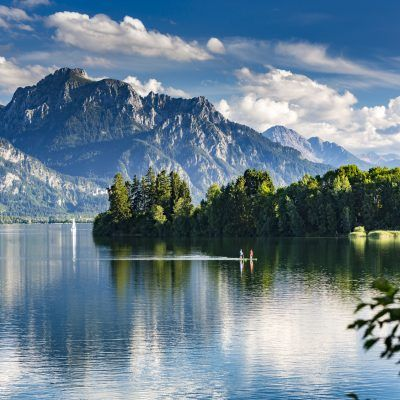 Germany, Allgäu, Forggensee lake, panorama with 2 standing up paddlers
