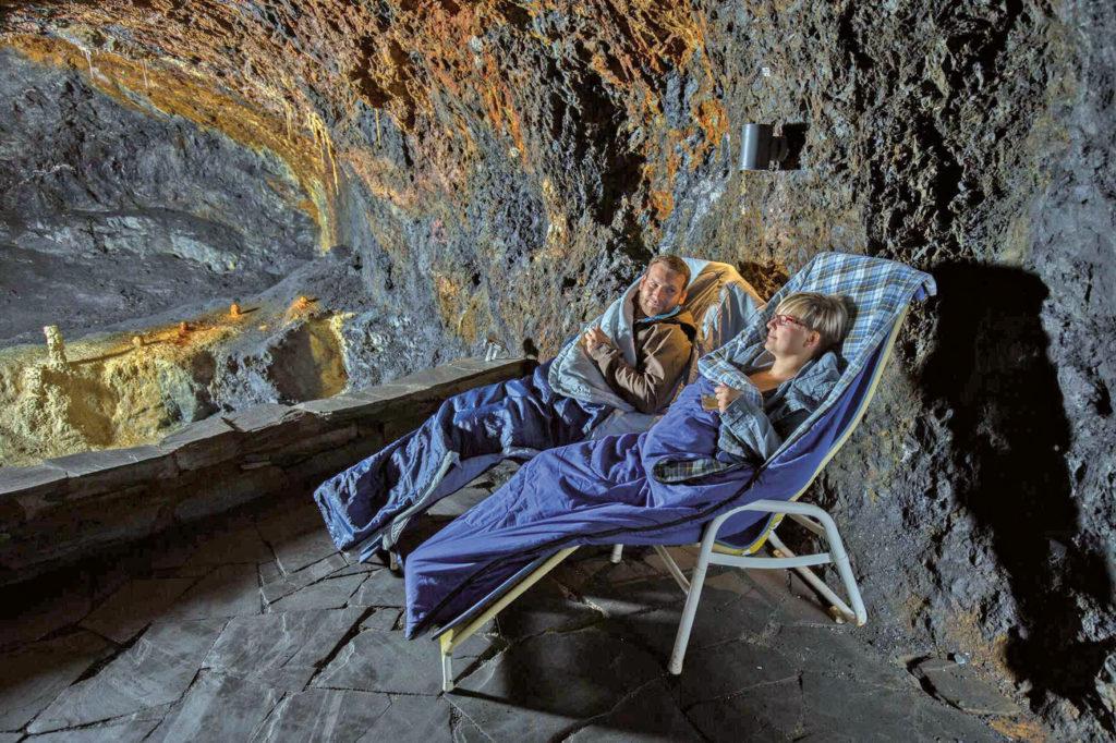 Ein Mann und eine Frau liegen im Heilstollen der Saalfelder Feengrotten in Liegestühlen