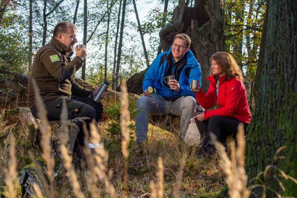 Ein Pärchen bei der gemeinsamen Pause mit einem Ranger auf dem Weitwanderweg Sauerland-Waldroute