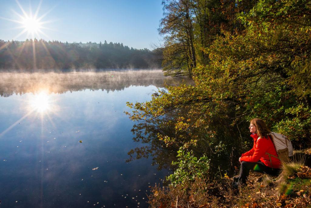 Eine Frau genießt den Sonnenaufgang am Möhnesee im Sauerland
