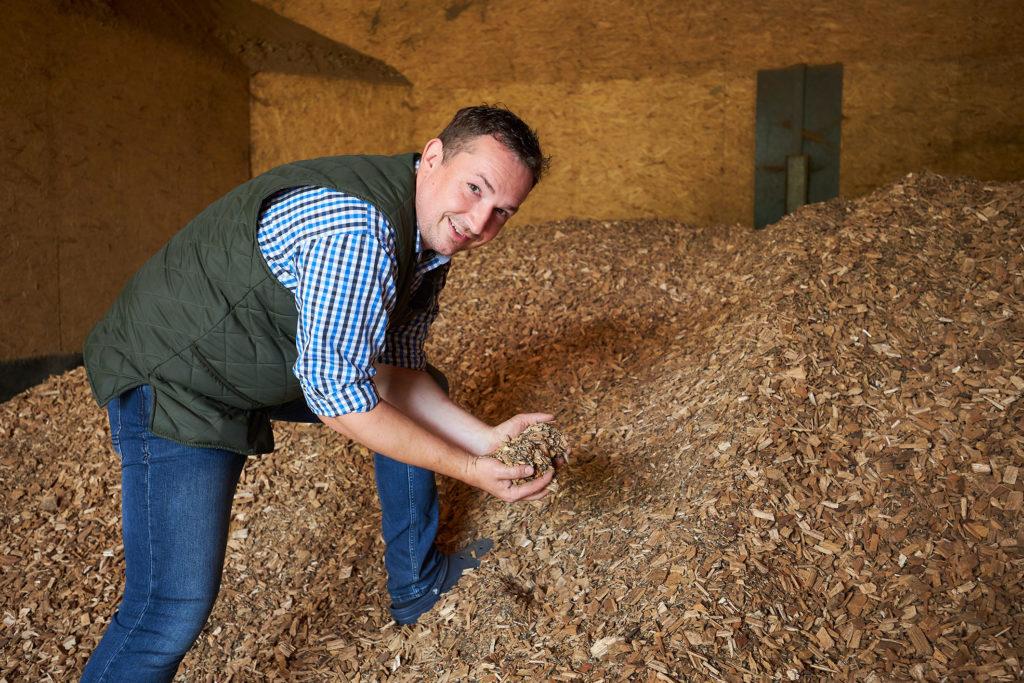 Henning Molt vom Flair Landhotel Strengliner Mühle in der Hackschnitzelanlage