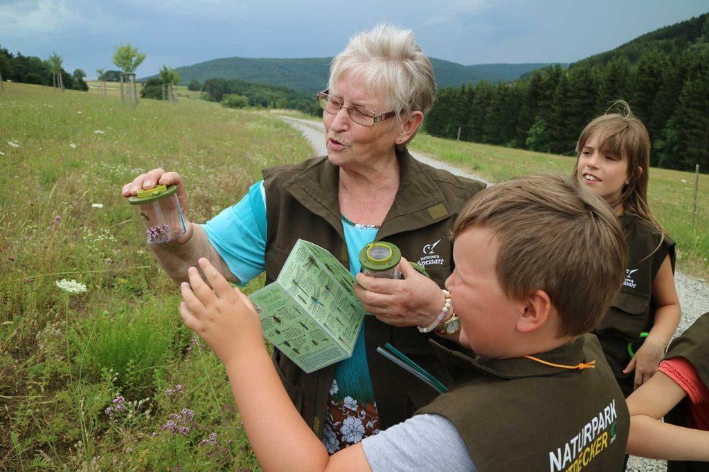 Eine Naturparkführerin im Spessart zeigt Kindern Tiere im Lupenglas