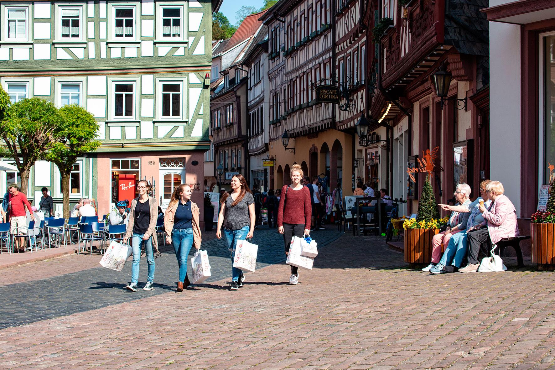 Vier Frauen laufen mit Einkaufstüten durch eine Straße in Miltenberg