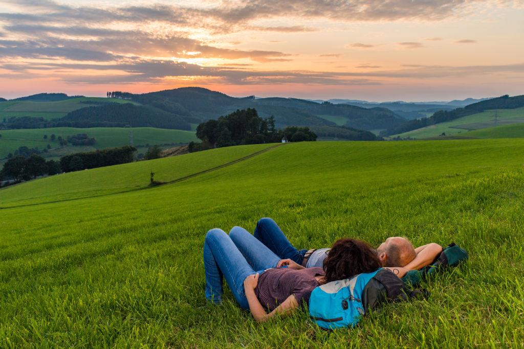 Wanderer genießen den Sonnenuntergang über dem Hennetal bei Oberhenneborn - so idyllisch sind Wanderausflüge im Sauerland