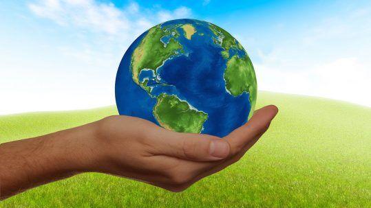 Eine Hand hält eine Weltkugel in der Hand.