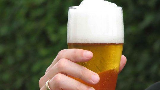 Eine Hand hält ein Glas mit Bier