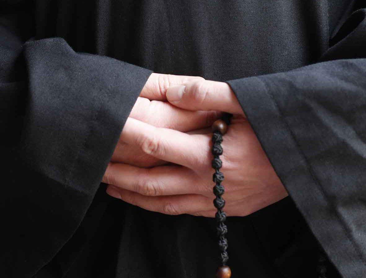 Hände eines Mönches mit Rosenkranz.