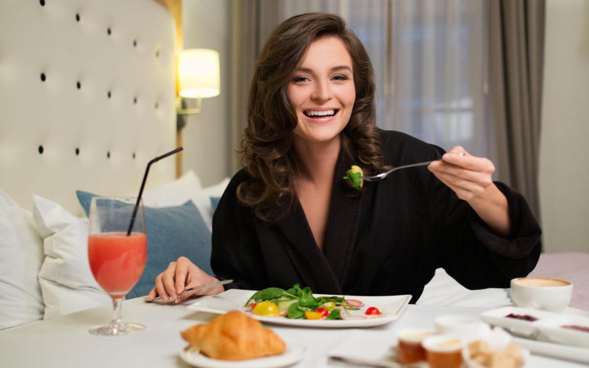 Frau frühstückt auf ihrem Hotelzimmer