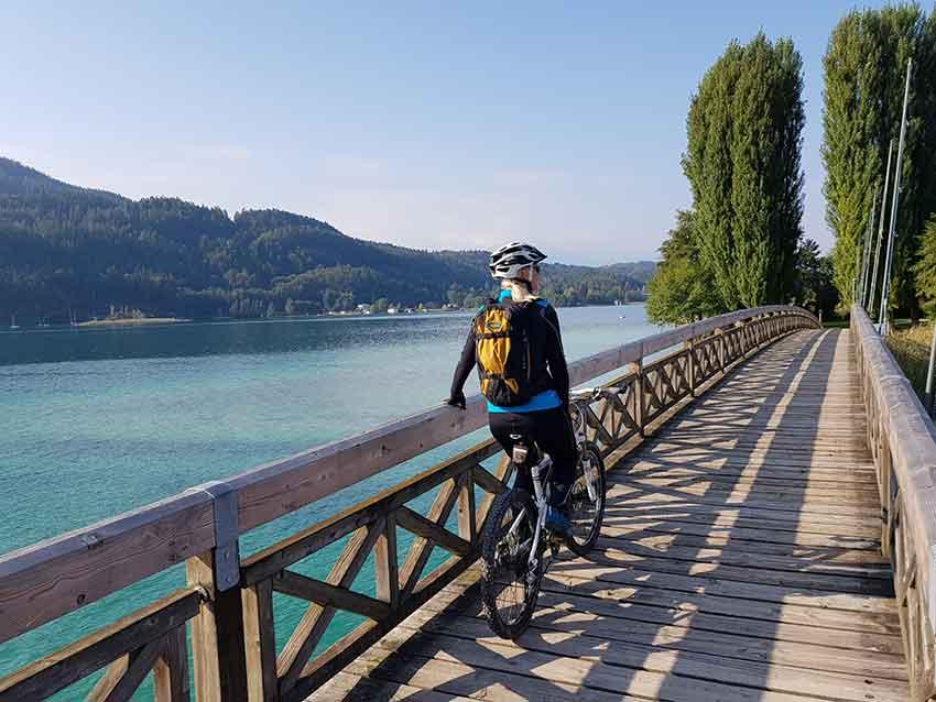 Radfahrer macht Pause auf einer Brücke über den Wörthersee