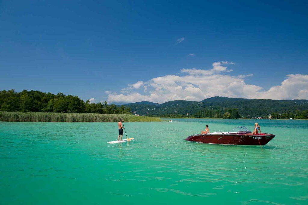 Stand-up Paddler und Motorboot auf dem Wörthersee